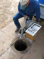 Man taking a water quality sample from a town well